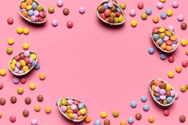 Bonbons gemmes colorés remplis dans les oeufs de pâques cassés sur fond rose avec un espace pour écrire le texte au centre Photo gratuit