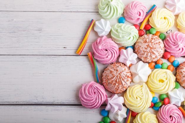 Bonbons multicolores mélangés sur fond en bois blanc. Photo Premium