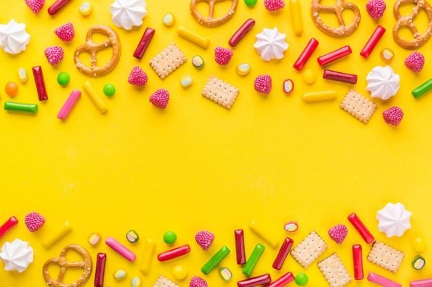 Bonbons à plat poser sur fond jaune Photo Premium