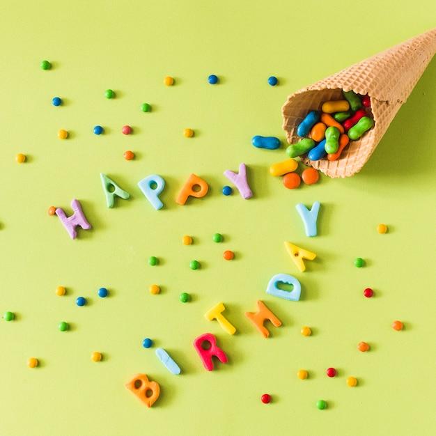 Bonbons renversant du cornet de crème glacée gaufre joyeux anniversaire sur une surface verte Photo gratuit