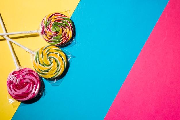 Bonbons sucettes colorées sur fond coloré rayé Photo gratuit