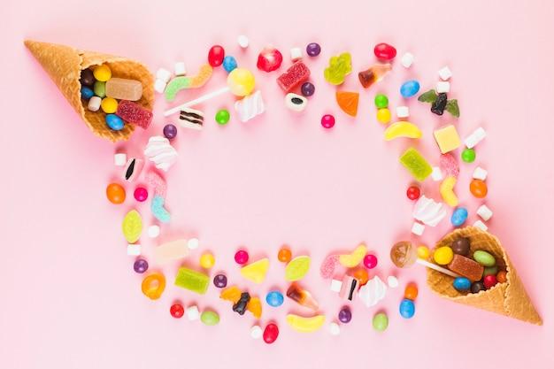 Bonbons sucrés colorés avec deux cônes de gaufre sur une surface rose Photo gratuit