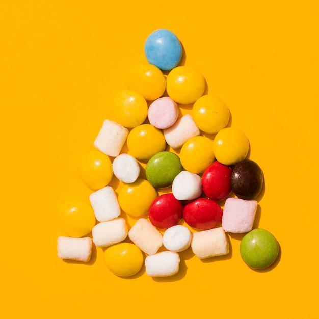 Bonbons triangle avec guimauves blanches sur fond jaune Photo gratuit