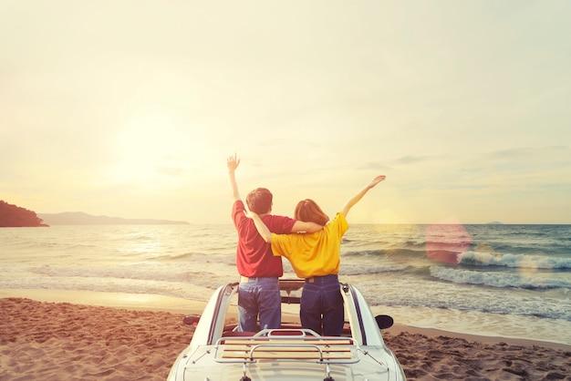 Bonheur jeune couple en voiture sur la plage tropicale au coucher du soleil. concept de temps de voyage et vacances d'été. Photo Premium