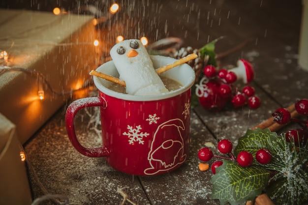 Bonhomme de neige dans la tasse à café sous une pluie de poudre blanche Photo gratuit