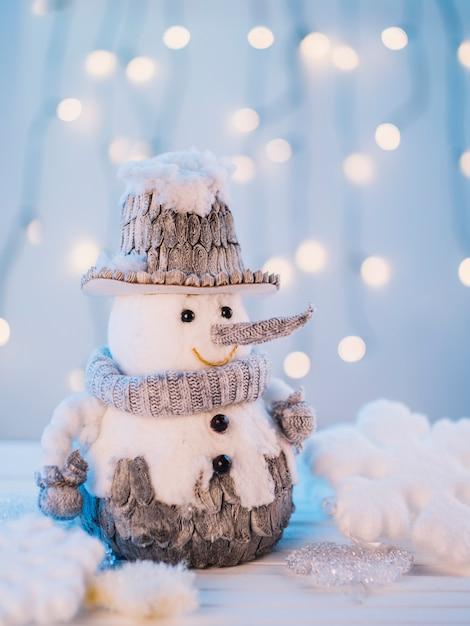Bonhomme de neige petit jouet sur une table blanche Photo gratuit