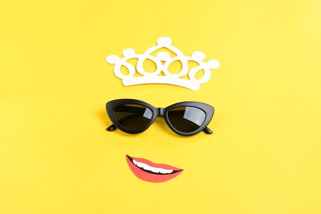 Bonjour l'été, le soleil avec des lunettes de soleil noires élégantes, une couronne, une bouche souriante sur jaune Photo Premium