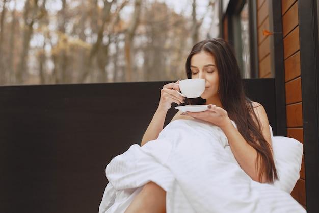 Bonjour. Femme Dans Une Couverture. Dame Assise Sur La Terrasse. Brunette Boit Un Café. Photo gratuit