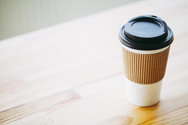 Bonjour, heure du café, café à emporter et haricots sur un fond en bois Photo Premium