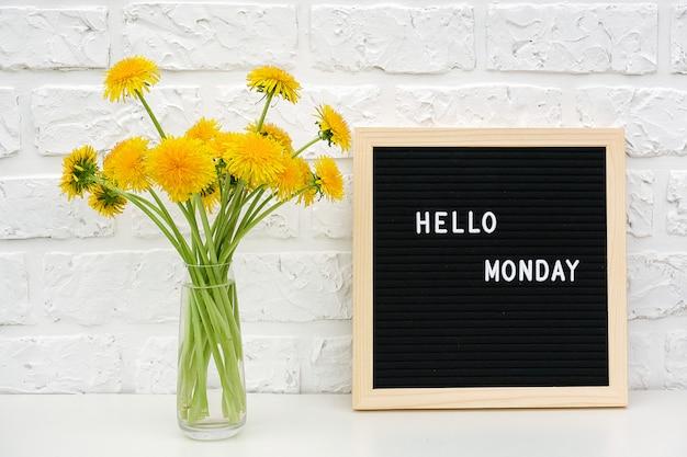 Bonjour lundi mots sur le tableau noir et bouquet de fleurs de pissenlits jaunes Photo Premium