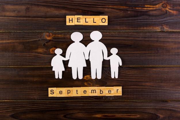 Bonjour mot de septembre avec la silhouette de papier de la famille. Photo Premium