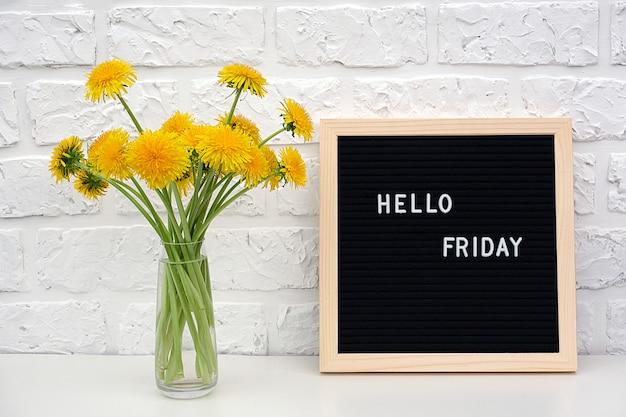 Bonjour vendredi mots sur tableau noir et bouquet de fleurs de pissenlits jaunes Photo Premium