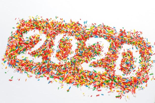 Bonne année 2020. forme de numéro coloré avec des éclaboussures de sucre arc-en-ciel brillant isolé sur blanc Photo gratuit