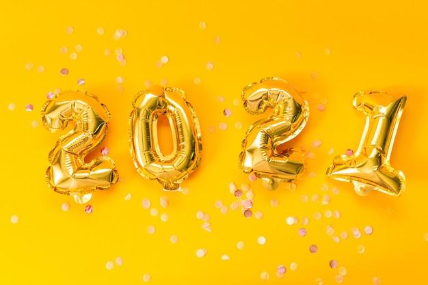 Photo Premium | Bonne Année 2021. Ballons D'or Brillant Avec Des étoiles Scintillantes Sur Fond Jaune.