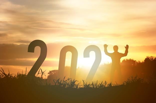 Bonne Année 2021 Silhouette Concept Humain Debout Avec Numéro Avec Beau Ciel Orange Pour Le Changement à La Nouvelle Année 2021. Photo Premium