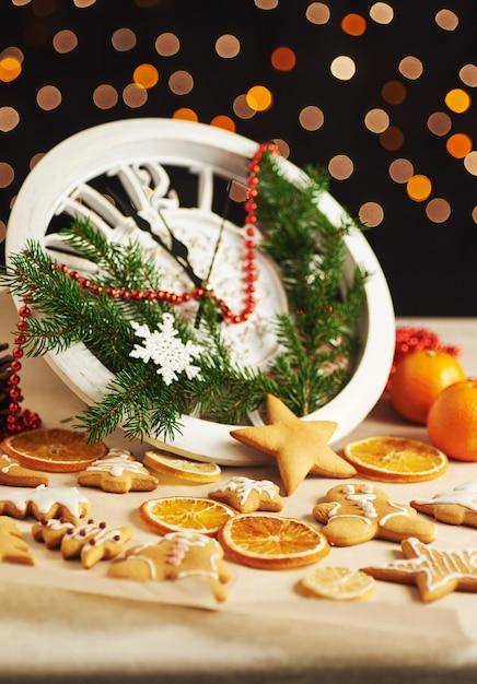 Bonne Année à Minuit, Vieille Horloge En Bois Avec Des Lumières De Vacances Et Des Branches De Sapin. Cuisiner Et Décorer Des Biscuits De Pain D'épice De Noël Et Des Tranches D'orange Frites Photo Premium