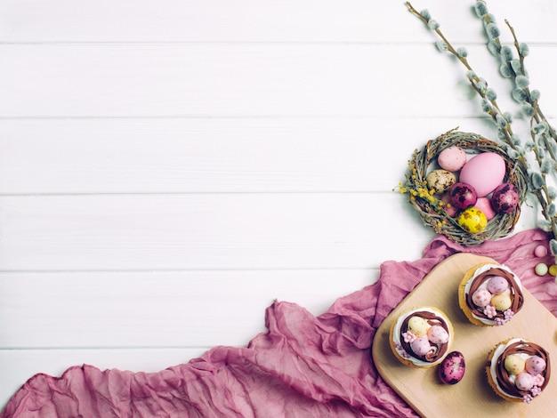 Bonne carte de pâques avec petits gâteaux au nid, œufs peints et brunchs en fleurs de saule Photo Premium