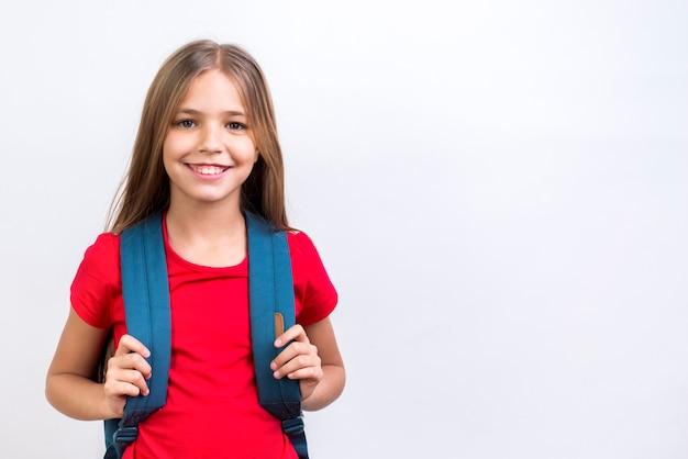 Bonne écolière avec sac à dos, souriant à la caméra Photo gratuit