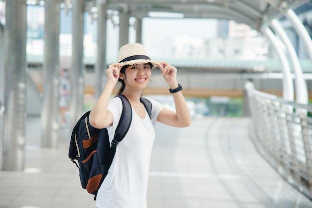Bonne étudiante asiatique souriante avec sac à dos au fond de la ville Photo gratuit