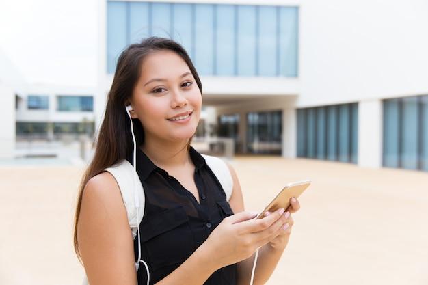 Bonne étudiante en écoutant de la musique sur cellule Photo gratuit