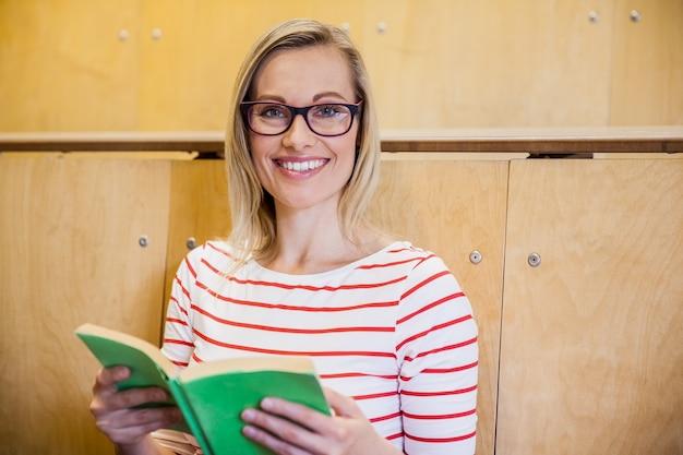 Bonne étudiante en lisant un livre à l'université Photo Premium