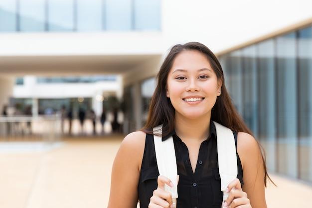 Bonne étudiante positive marchant dehors Photo gratuit