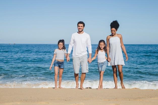 Bonne famille posant et tenant la main Photo gratuit