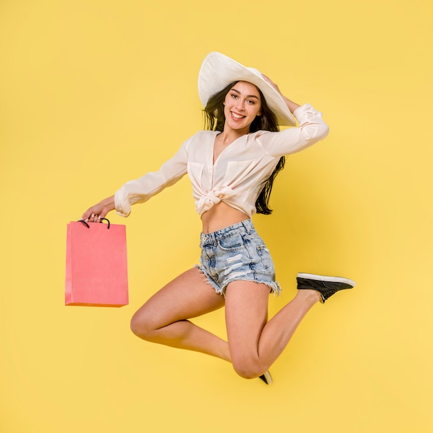Bonne femme sautante au chapeau blanc Photo gratuit