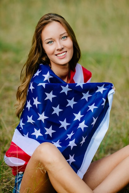 Bonne Fille Est Assise Sur L'herbe Avec Le Drapeau Américain Photo gratuit