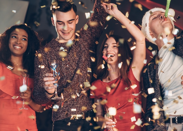 Bonne Humeur. Air Dans Les Confettis. Quatre Bons Amis Bien Vêtus Sont à La Fête Du Nouvel An Photo Premium