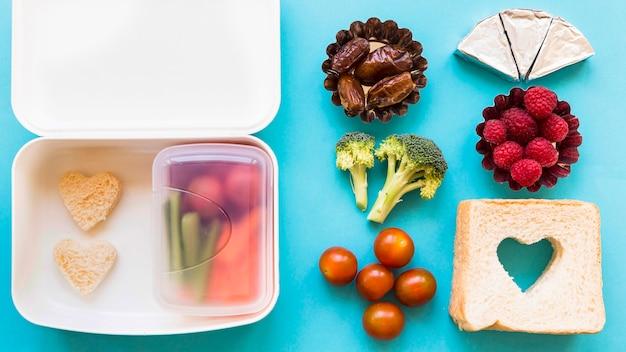 Bonne nourriture près de la boîte à lunch ouverte Photo gratuit