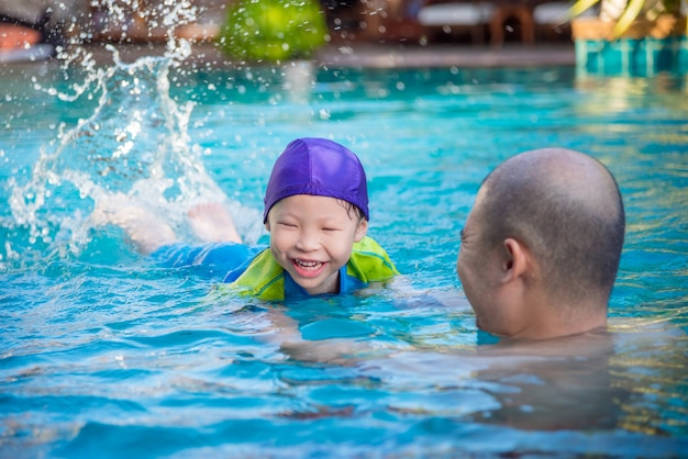 Bonne petite fille asiatique apprendre à nager avec son père dans la piscine Photo Premium