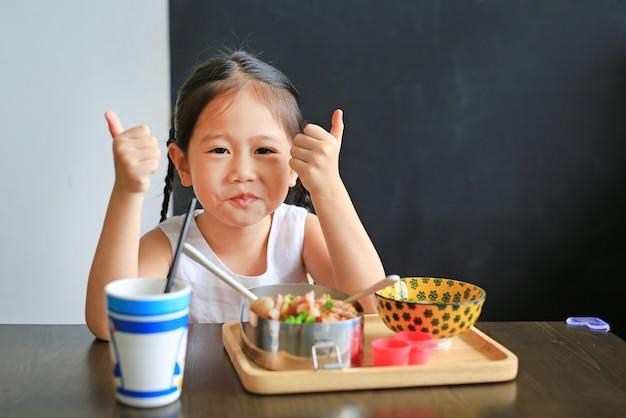 Bonne petite fille asiatique enfant manger du riz par soi-même dans le restaurant. Photo Premium