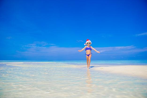 Bonne petite fille au bonnet de noel sur la plage pendant les vacances Photo Premium