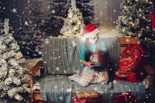 Bonne petite fille au chapeau de père noël avec présent sur le canapé. Photo Premium