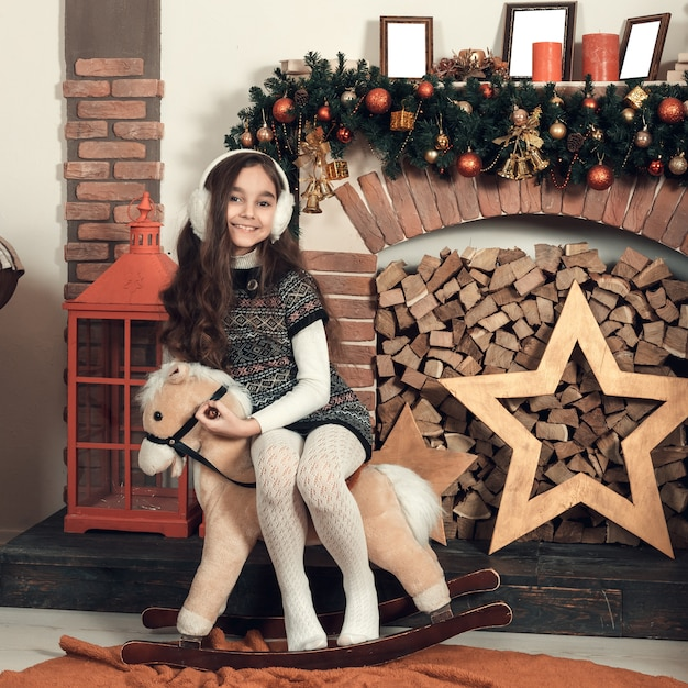 Bonne petite fille brune aux cheveux longs, assise sur un cheval de jouet à la salle décorée de noël. Photo Premium