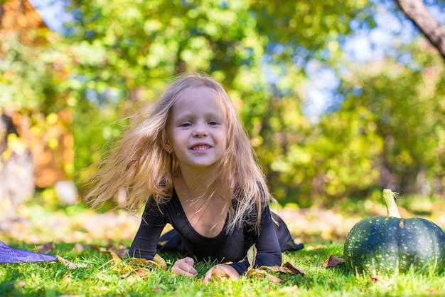 Bonne petite fille en costume d'halloween avec citrouille jack.trick ou traiter Photo Premium