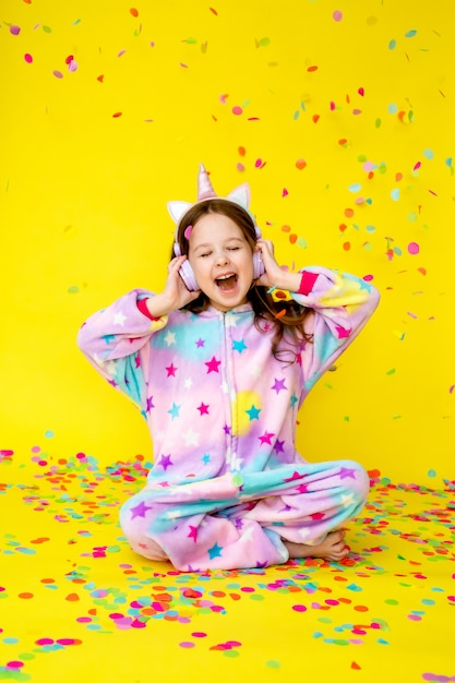 Bonne Petite Fille Dans Une Licorne Kigurumi Sur Fond Jaune Photo Premium