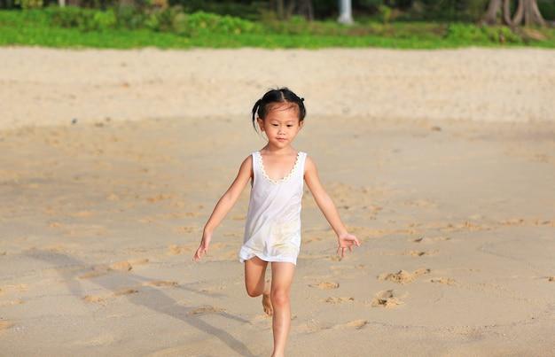 Bonne petite fille enfant en cours d'exécution sur la plage Photo Premium