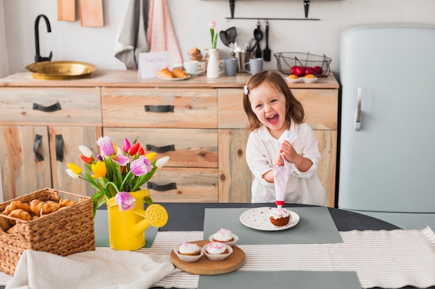 Bonne petite fille faisant des cupcakes Photo gratuit