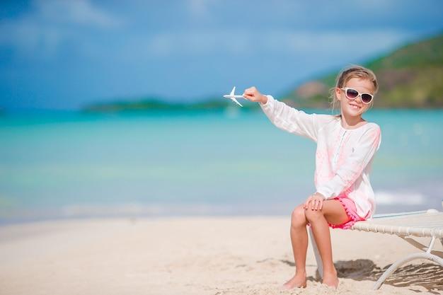 Bonne Petite Fille Avec Jouet Avion En Mains Sur La Plage De Sable Blanc. Kid Jouer Avec Des Jouets Sur La Plage Photo Premium