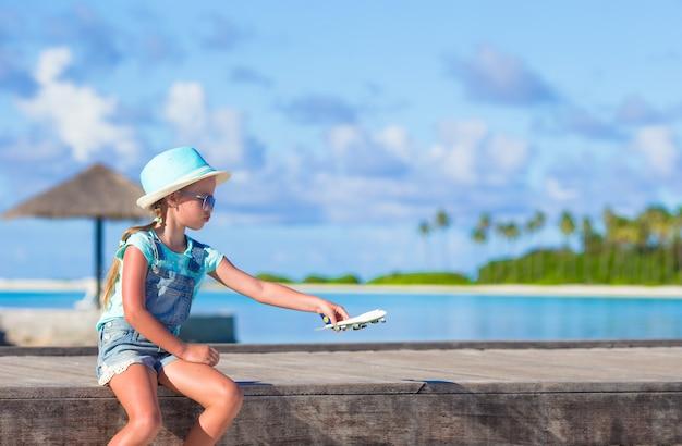 Bonne Petite Fille Avec Jouet Avion En Mains Sur La Plage De Sable Blanc Photo Premium