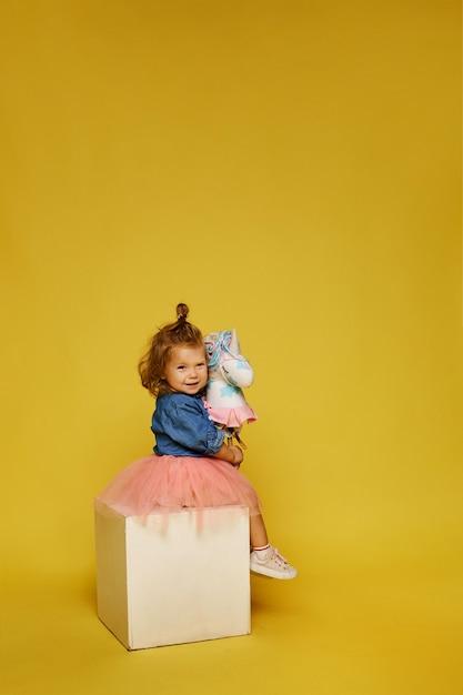 Bonne Petite Fille En Jupe Rose Et Veste En Jean Avec Un Cheval Jouet Sur Le Mur Jaune Photo Premium