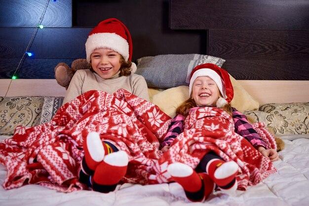 Bonne Petite Fille Sur Le Lit En Attente De Noël. Photo Premium
