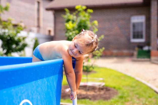 Bonne petite fille en maillot de bain rouge sautant dans la piscine en plein air à la maison. petite fille apprend à nager. plaisir de l'eau pour les enfants. Photo Premium