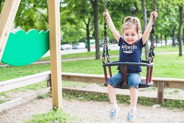 Bonne petite fille profitant de la balançoire Photo gratuit