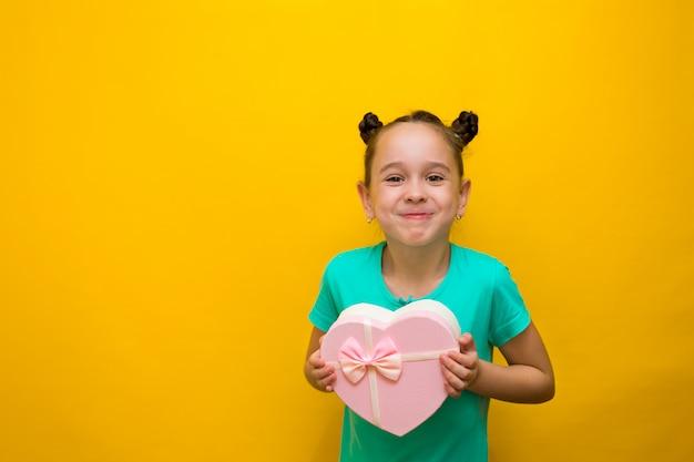 Bonne Petite Fille Avec Des Queues Debout Isolé Sur Un Mur Jaune Tenant Un Sac Rose Shopping. Sourit Pensivement Photo Premium