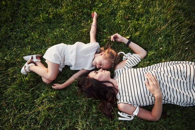 Bonne Petite Fille Et Sa Mère S'amusant à L'extérieur Sur L'herbe Verte En Journée D'été Ensoleillée. Photo gratuit