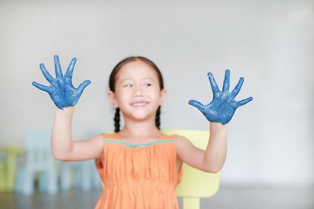 Bonne Petite Fille Avec Ses Mains Bleues Dans La Peinture Dans La Chambre Des Enfants. Concentrez-vous Sur Les Mains De Bébé. Photo Premium