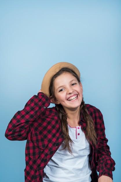 Bonne petite fille tenant un chapeau sur la tête Photo gratuit